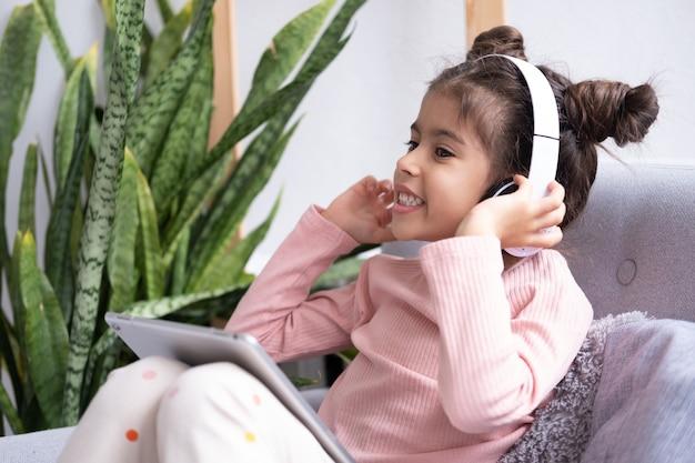 Garotinha feliz sorridente usando tablet em fones de ouvido sem fio no sofá em casa
