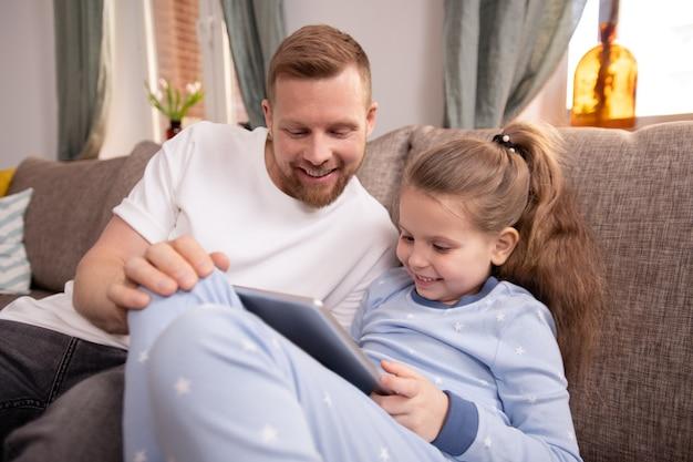 Garotinha fofa com touchpad e seu pai vendo filmes ou desenhos online enquanto fica em casa em quarentena