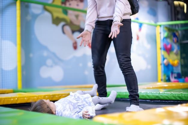 Garotinha fofa pulando em um trampolim com a mãe e rindo no parquinho infantil