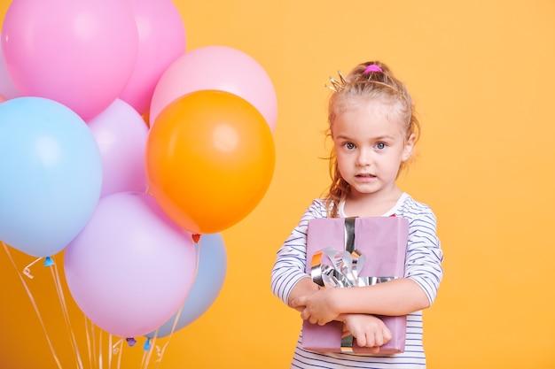 Garotinha fofa segurando um presente embrulhado, ao lado de um monte de balões coloridos na parede amarela
