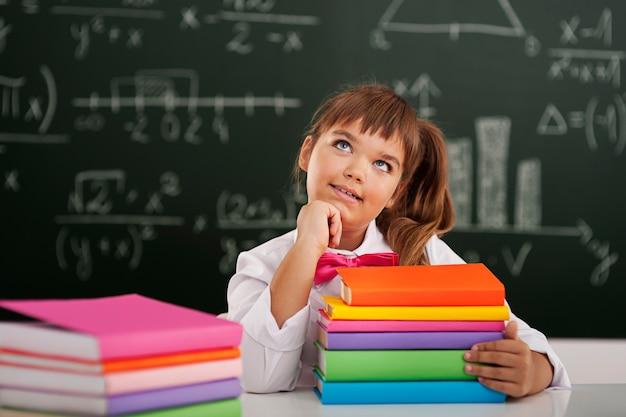 Garotinha fofa sentada na sala de aula com seus livros e sonhando