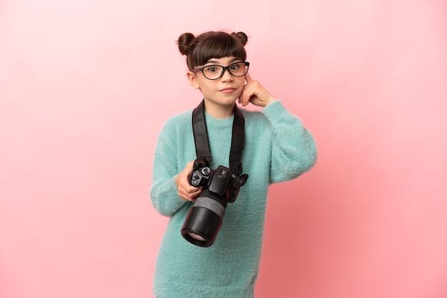 Garotinha fotógrafa isolada em um fundo rosa pensando em uma ideia