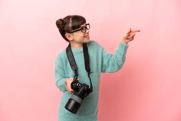 Garotinha fotógrafa isolada em uma parede rosa apontando o dedo para o lado e apresentando um produto