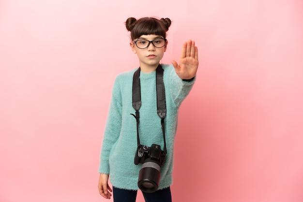 Garotinha fotógrafa isolada em uma parede rosa fazendo um gesto de parada