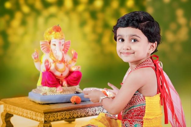 Garotinha indiana com o senhor ganesha e orando, festival indiano de ganesh