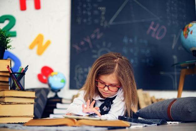 Garotinha inteligente com tablet digital na sala de aula.