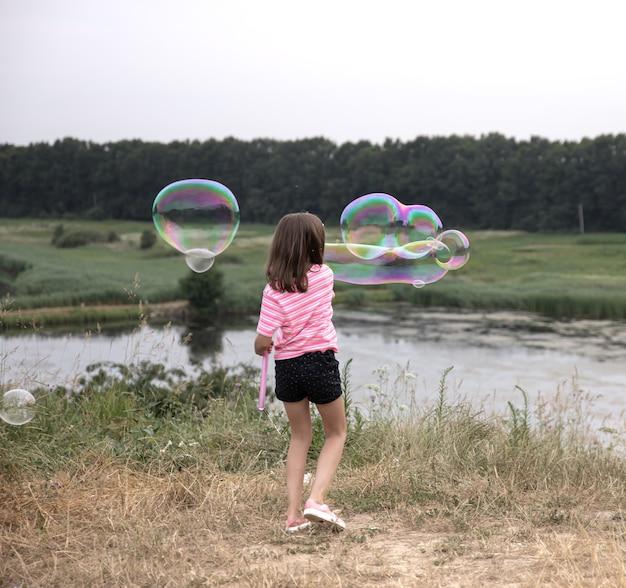Garotinha lança bolhas de sabão enormes na bela natureza do fundo, vista traseira.