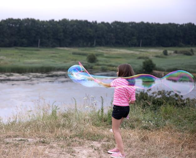 Garotinha lança bolhas de sabão enormes na bela natureza do fundo.
