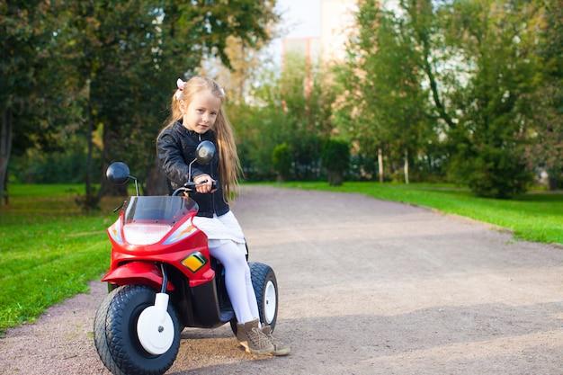 Garotinha linda rocha na jaqueta de couro sentado em sua moto de brinquedo