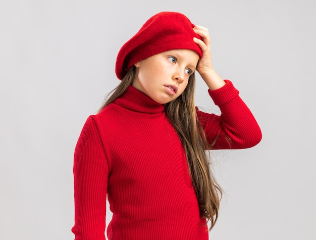 Garotinha loira ansiosa em pé na vista de perfil, usando uma boina vermelha, mantendo a mão na cabeça, olhando para o lado isolado na parede branca com espaço de cópia