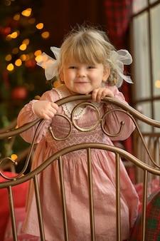 Garotinha loira bonita em pé na cabeceira da cama de ferro