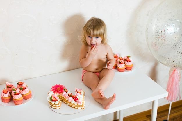 Garotinha loira de dois anos de idade em calças rosa sentada na mesa branca perto de seu bolo de aniversário e diferentes doces rosa na mesa