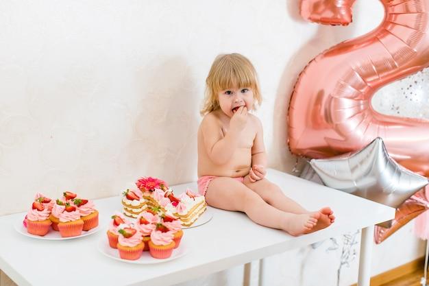 Garotinha loira de dois anos de idade usando calça rosa sentada na mesa branca