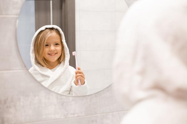 Garotinha loira de roupão branco escovando os dentes na frente do espelho do banheiro