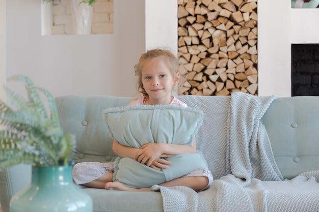 Garotinha loira em um apartamento elegante e espaçoso com um design elegante em tons pastel verdes, cinza e brancos com uma grande janela e paredes decorativas