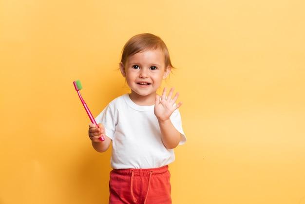 Garotinha loira escova os dentes com pasta de dente. fundo amarelo. o conceito de higiene dental.