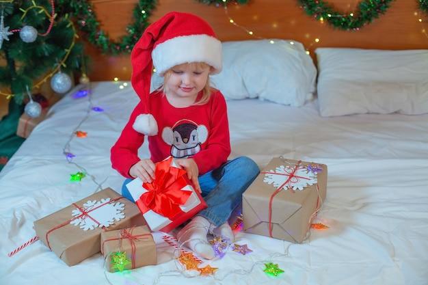 Garotinha loira feliz abrindo presentes de natal, sentada na cama em casa.