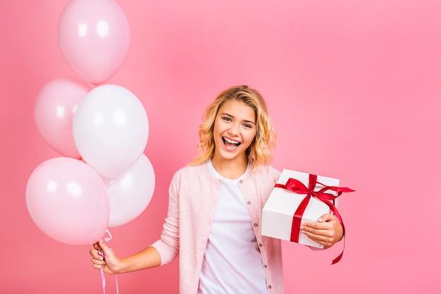 Garotinha loira feliz com balões comemorando feriados