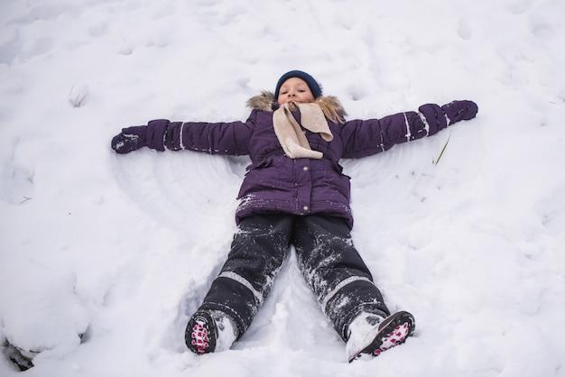 Garotinha loira feliz deita-se na neve e faz um anjo, criança se divertindo brincando com neve em dia de inverno