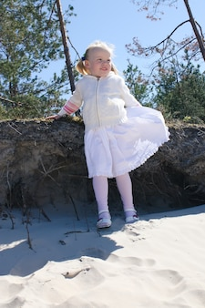 Garotinha loira feliz em um vestido branco caminha na praia na costa do mar báltico.