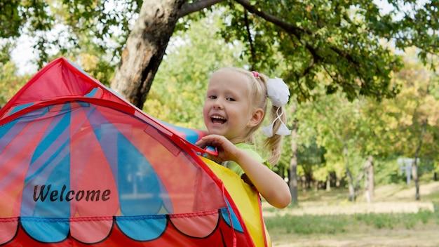 Garotinha loira fofa rindo olhando por cima de uma tenda colorida armada ao ar livre no parque