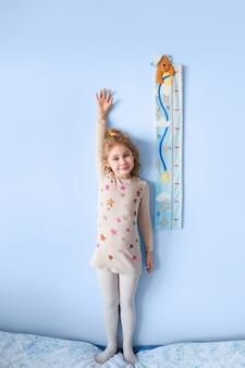 Garotinha loira medindo a altura contra a parede da sala.