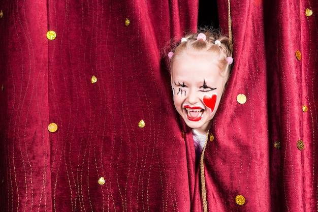 Garotinha loira muito animada no palco esperando para fazer sua entrada no palco durante uma apresentação espiando por entre as cortinas e rindo