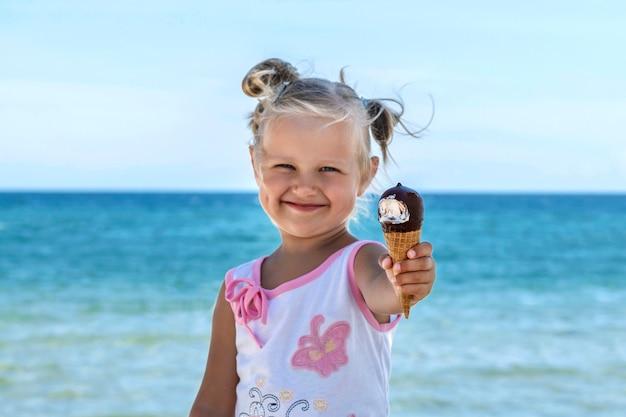 Garotinha loira na praia segurando sorvete de chocolate