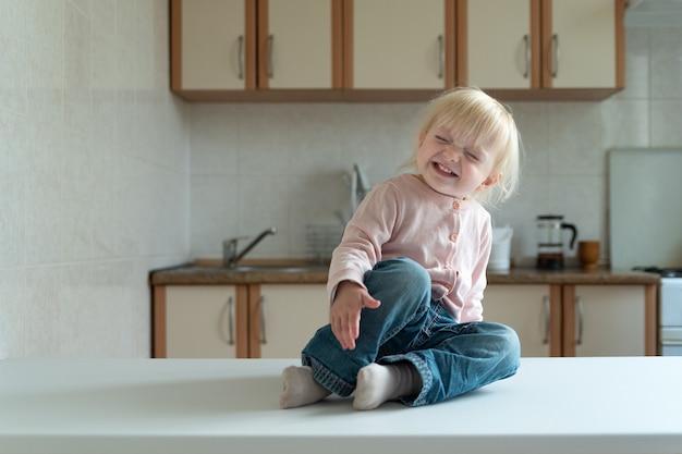 Garotinha loira se senta na cozinha e rindo. criança feliz.