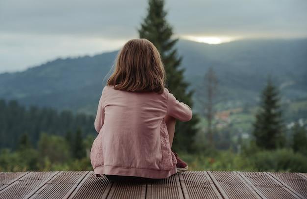 Garotinha loira sentada no terraço olhando o pôr do sol atrás das montanhas