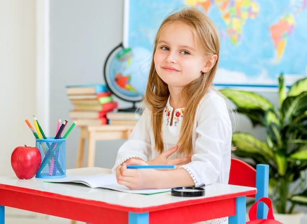Garotinha loira sentar na mesa branca e rindo na sala de aula da escola