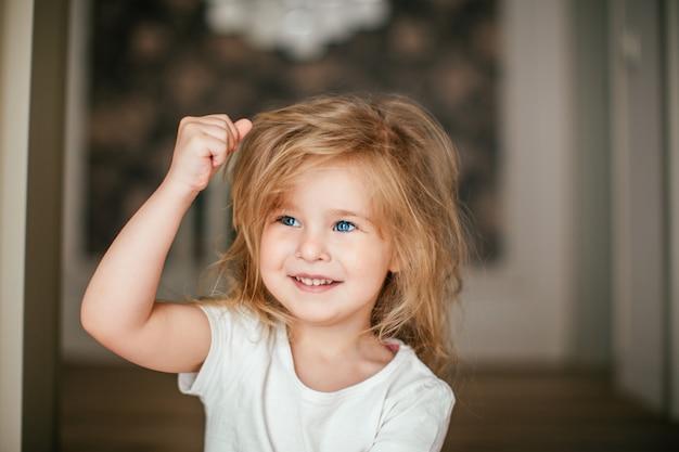 Garotinha loira shaggy com uma mão para cima está sorrindo depois de acordar de manhã