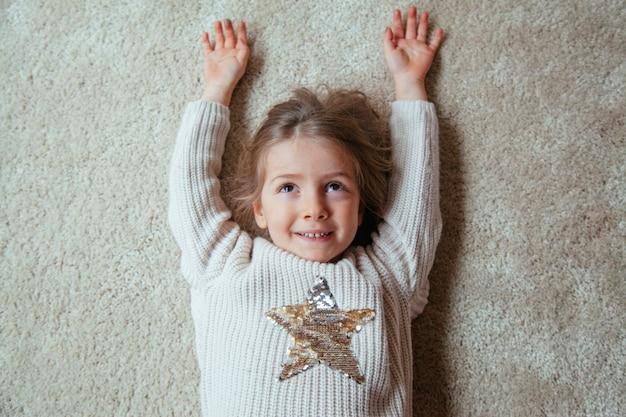 Garotinha loira sorrindo com uma estrela na camisola dela