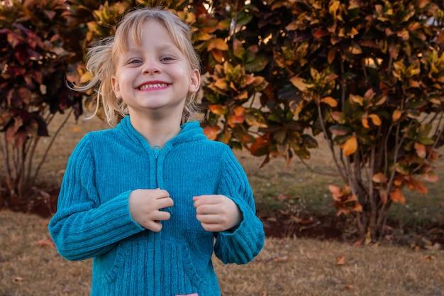 Garotinha loira sorrindo para a câmera com um agasalho frio no jardim