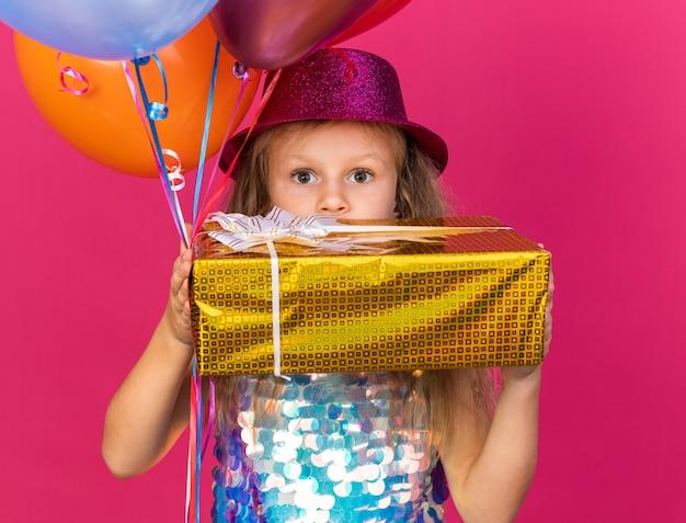 Garotinha loira surpresa com chapéu de festa roxo segurando balões de hélio e uma caixa de presente na frente do rosto, isolado na parede rosa com espaço de cópia