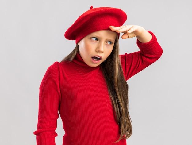 Garotinha loira surpresa e impressionada de boina vermelha olhando para um lado distante, isolada na parede branca