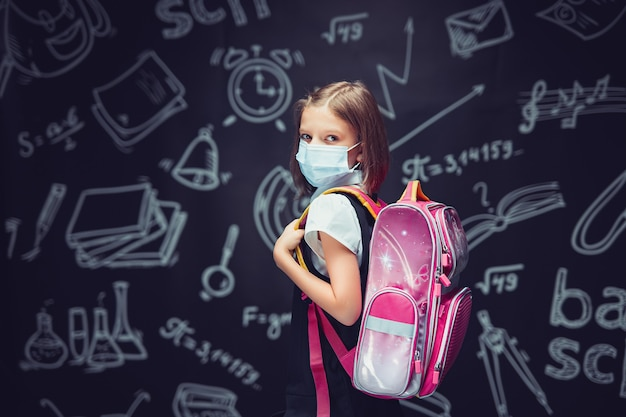 Garotinha menina em uniforme escolar usando máscara médica com mochila no fundo do quadro-negro