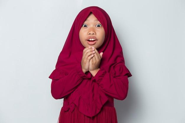 Garotinha muçulmana asiática chocada com a sensação de surpresa isolada no fundo branco