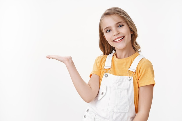 Garotinha muito esperta, criança com penteado loiro em camiseta amarela e macacão segurando algo na palma da mão, apresenta o produto em branco, espaço em branco, sorrindo alegre, gabando-se do presente de aniversário dela