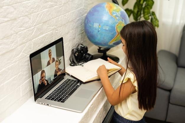 Garotinha olhando para a tela do laptop com expressão de surpresa e entusiasmo. garotinha inteligente e sorridente fazendo anotações. comunicação no conceito de negócio.