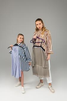 Garotinha orgulhosa e animada carregando um vestido azul enquanto experimenta com a irmã mais velha e os mostra em cabides