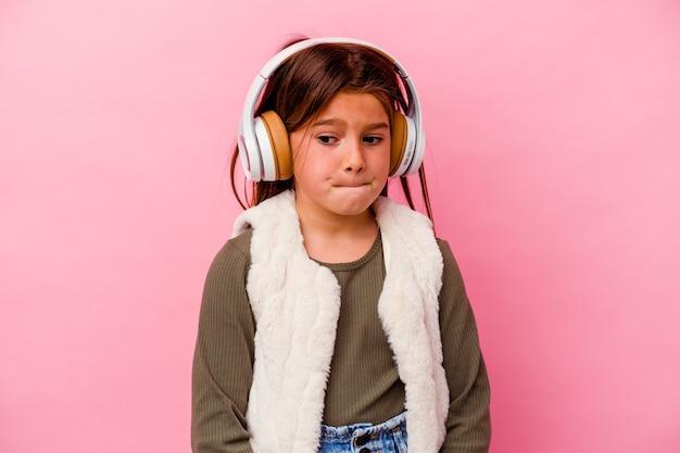 Garotinha ouvindo música isolada na parede rosa confusa, duvidosa e insegura