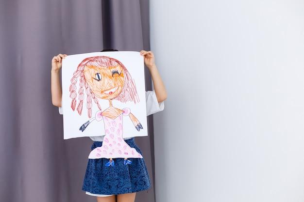 Garotinha pré-escolar segurando uma foto de retrato