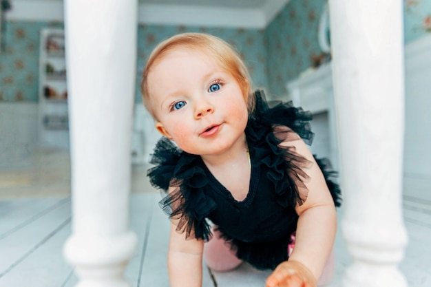 Garotinha rastejante de um ano de idade no chão em uma sala iluminada sorrindo e rindo
