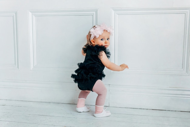 Garotinha rastejante de um ano de idade usando coroa de flores de primavera em pé no chão em uma sala iluminada