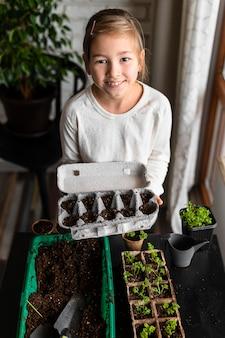 Garotinha segurando sementes plantadas em uma caixa de ovos em alto ângulo