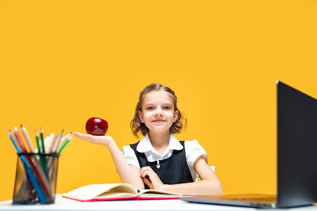 Garotinha segurando uma maçã na mão enquanto muda de roupa na aula online de educação à distância