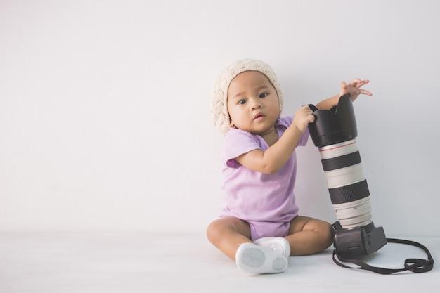 Garotinha, sentada no chão, segurando a câmera dslr