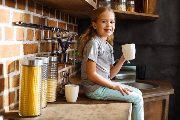 Garotinha simpática sorrindo enquanto bebia chá na cozinha
