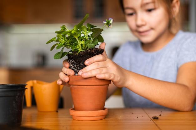 Garotinha sorridente plantando flores em um vaso em casa
